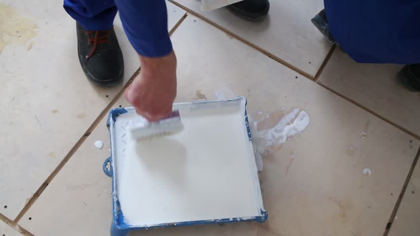 Worker dunks brush in the tray with glue on the floor - HD stock video clip