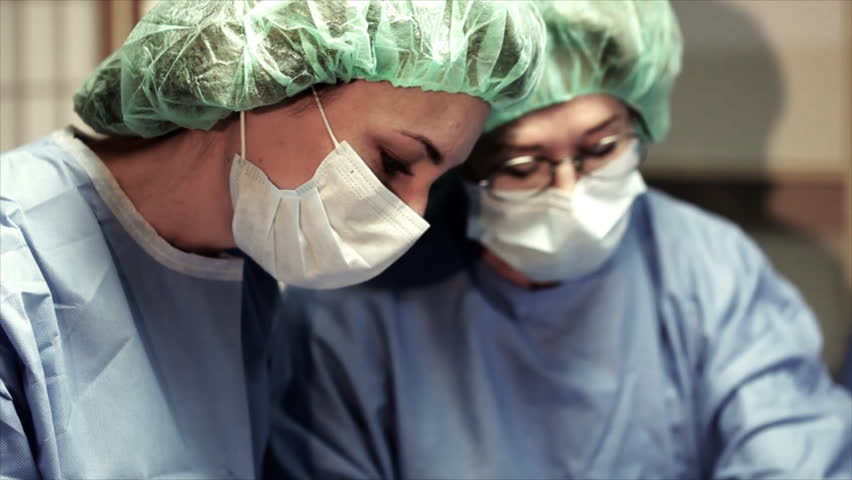 The camera tilts and pans revealing three surgeons engaged in a surgical procedure in an operating room. - HD stock video clip