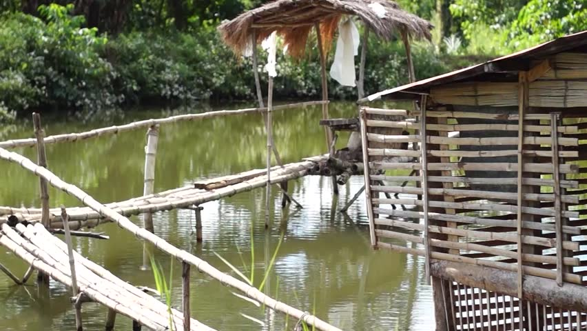 IFUGAO, PHILIPPINES - DECEMBER 24, 2014: Bamboo hut and bamboo bridge inside man-made fish pond