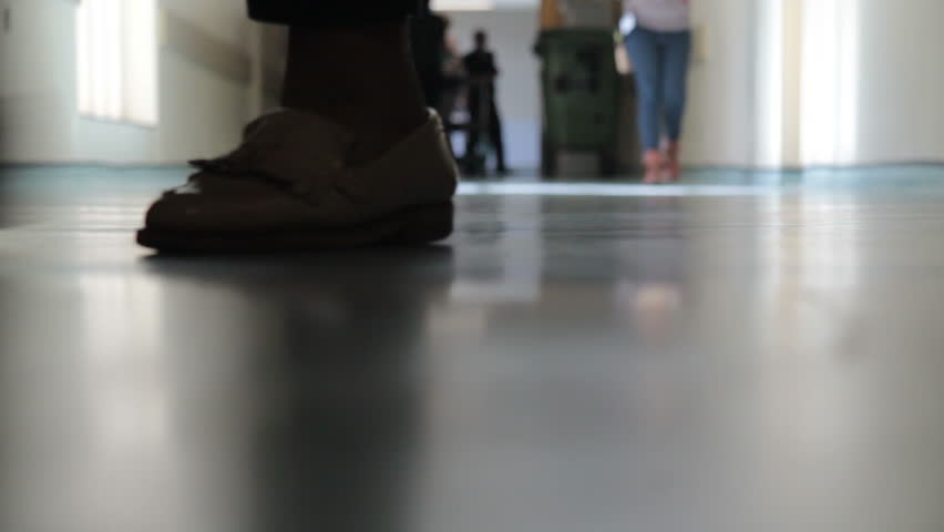 Low angle shot of Patients, Doctors, Nurses and helpers towards and away from a selective focused camera placed on the floor.