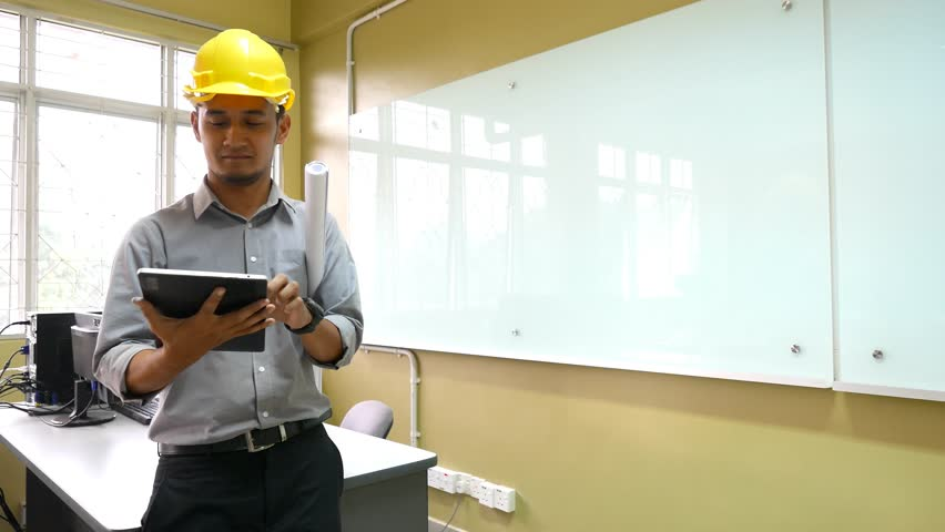 A young male architect using a tablet  with office environment.