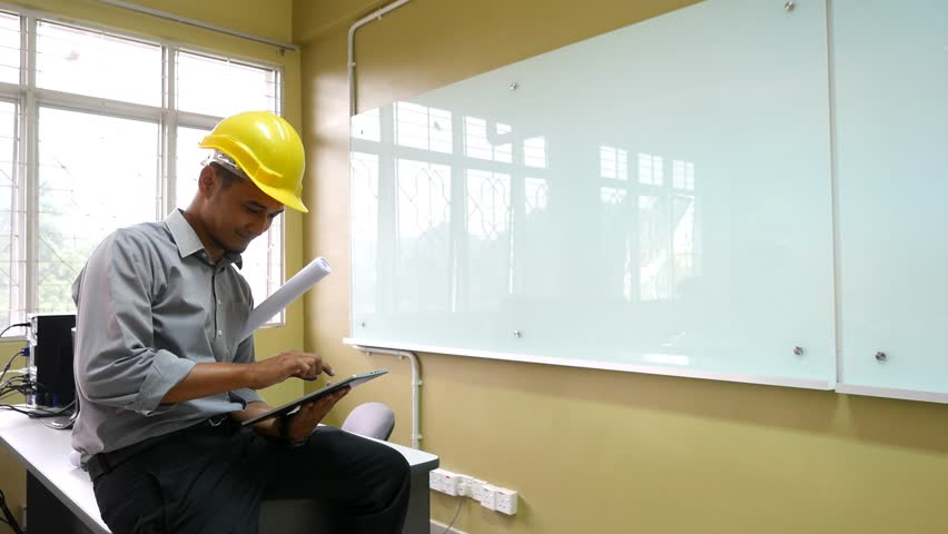 An architect using a tablet while sitting on the table with office environment, dolly shot.