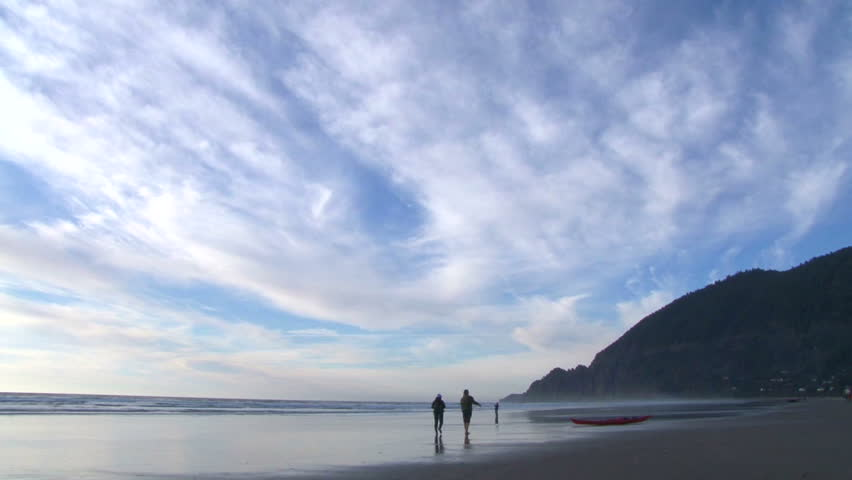 Unrecognizable people walking on sandy beach at the Pacific Coast in Manzanita, Oregon.