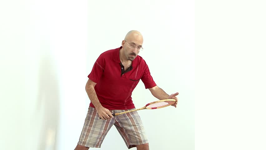 a bald man in a red shirt gets ready to play badminton,tennis,energetically Bouncing and waving his arms and communicates with facial expressions on the face