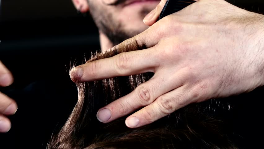 Male hand cut their hair. Lifted her hair and starts work with scissors. Action takes place in the barber shop
