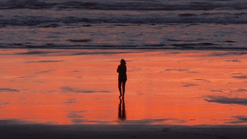 Silhouetted woman walking on sandy shores of the Oregon Coast at sunset.