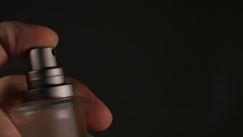 Fragrance luxury bottle contents in dark spraying slow motion 1080p FullHD video - Perfume bottle spray on black background 1920X1080 slow-mo footage