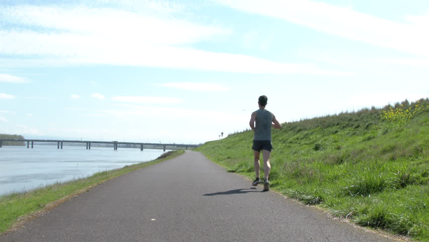 Unrecognizable man running down path along the Columbia River in Portland Oregon.