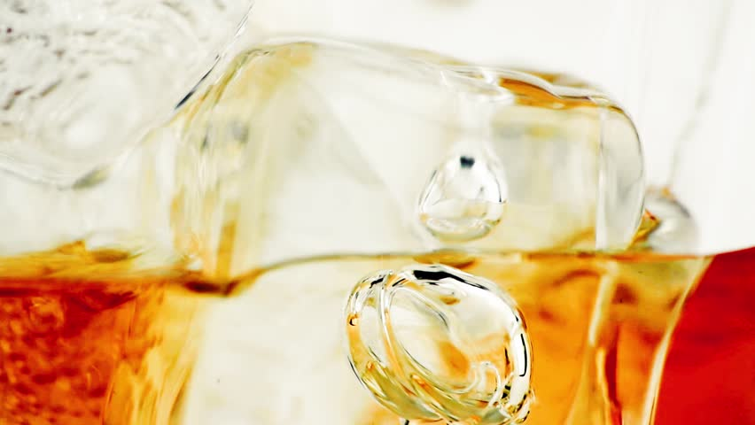 close-up of whiskey in glass with ice used for background, whisy texture - HD stock video clip