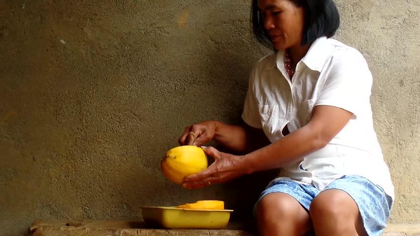 AGUINALDO, IFUGAO - APRIL 3, 2015: Adult woman peeling papaya fruit with knife