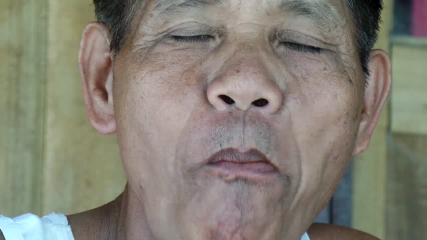 AGUINALDO, IFUGAO - APRIL 3, 2015: Mature man chewing betel nut smile