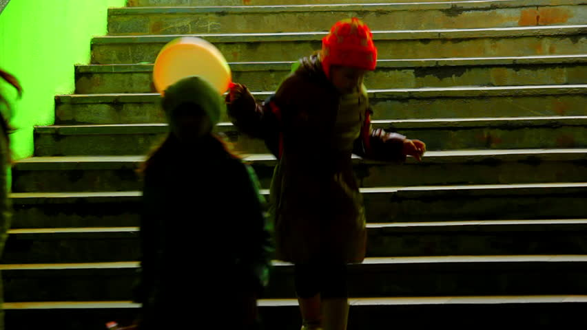 Three girls on dark green staircase. Three girls go down a dark scary tunnel. One of the girls cares a balloon. Source: Canon 7D, graded. Clip ID: ax1215c