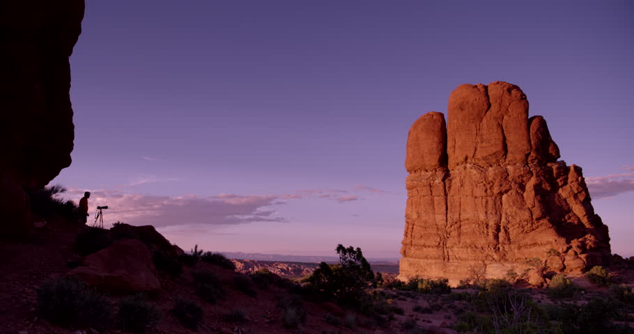 Arches National Park, Moab, Utah. Male photographer with camera on tripod shooting red sandstone monolith near Balanced Rock at sunset.