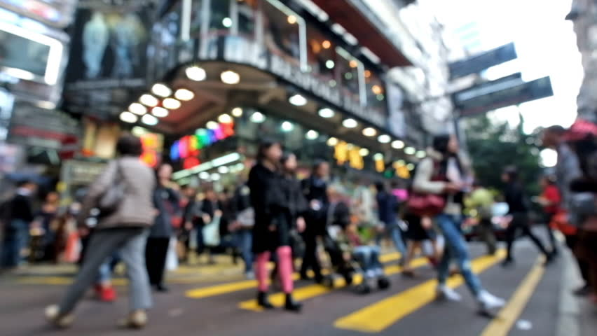 Abstract cityscape blurred background. Unrecognizable people walking on crosswalk in crowded city street with modern shopping malls Hong Kong. Blur effect