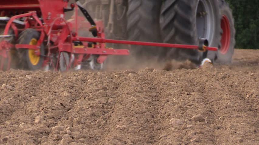 Soil earth and tractor fertilizing field. Heavy agricultural machinery. Static shot on Canon XA25. Full HD 1080p. Progressive scan 25fps. Tripod.