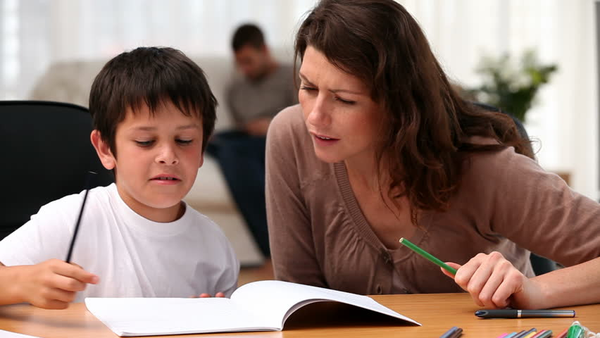 Mom helping his son to do his homework in the living room