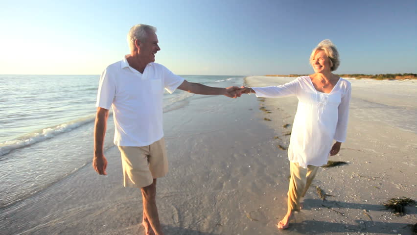 Carefree senior couple romantically dancing together on a beach at sunset - HD stock footage clip