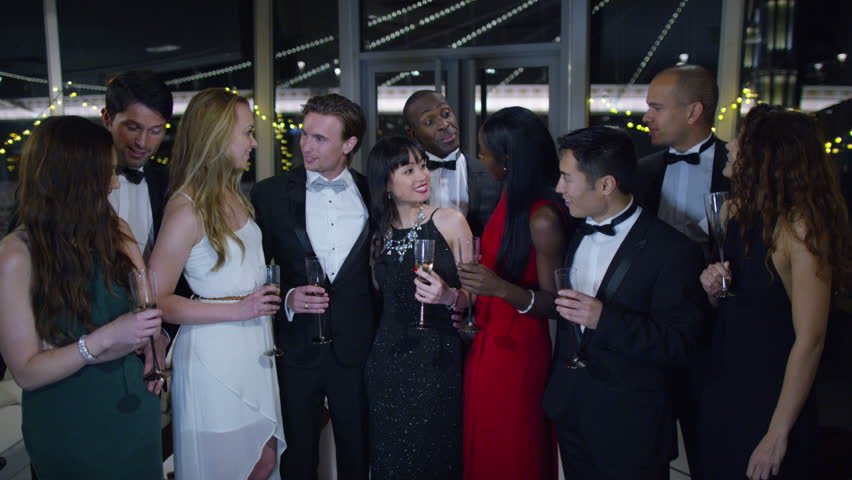 4K Portrait of attractive mixed ethnicity group of friends at glamorous party, with city lights in the background
