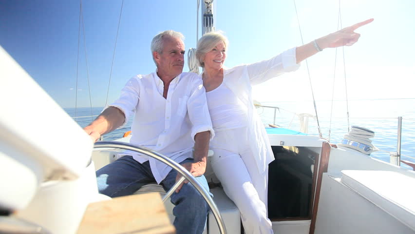 Healthy retired couple steering a course aboard their luxury sailing boat - HD stock footage clip