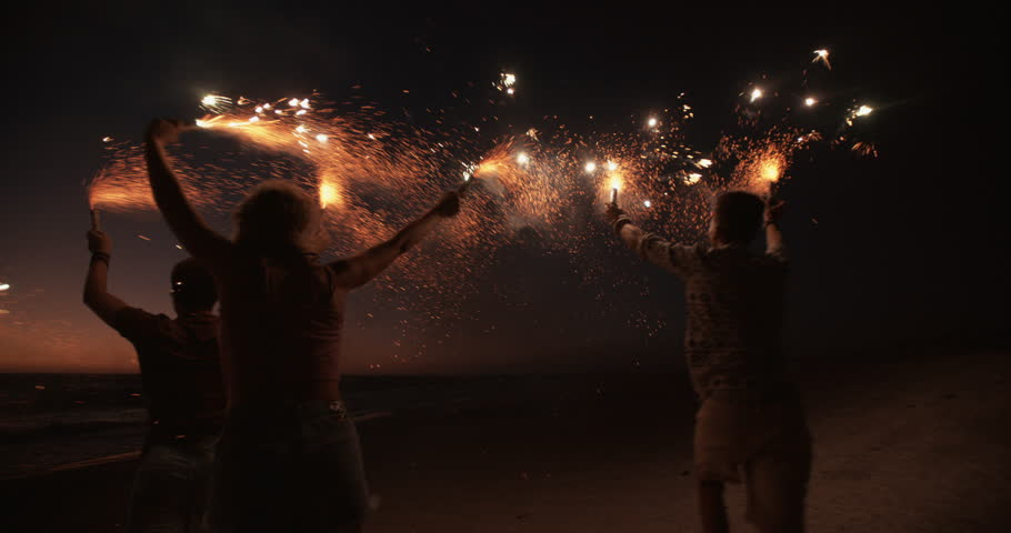 Rearview of friends running together on a beach holding sparkling fireworks in Slow Motion