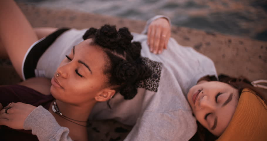 Cropped image of mixed race teen girl friends in grunge styling lying alongside water together , Panning in Slow Motion - 4K stock video clip