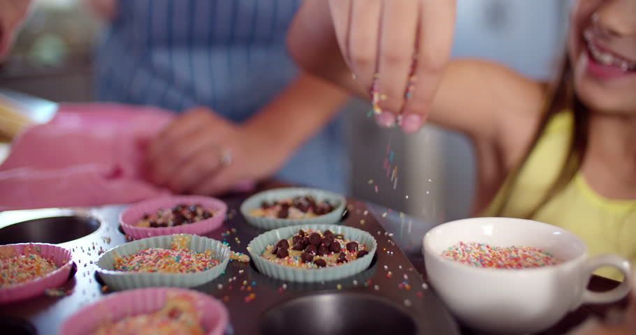 Cropped shot of the hans of a mom and daughter decorating cupcakes in a baking tray together, Panning in Slow Motion - 4K stock video clip