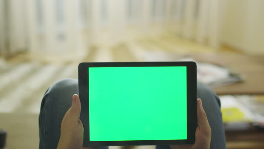 Man is Laying on Couch at Home and Holding Tablet with Green Screen in Landscape Mode on Lap. Shot on RED Cinema Camera in 4K (UHD).