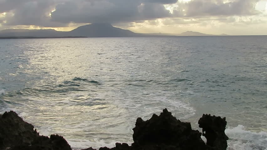 Waves crash on coral at sunset with view of Mount Isabel de Torres, Dominican Republic - HD stock footage clip