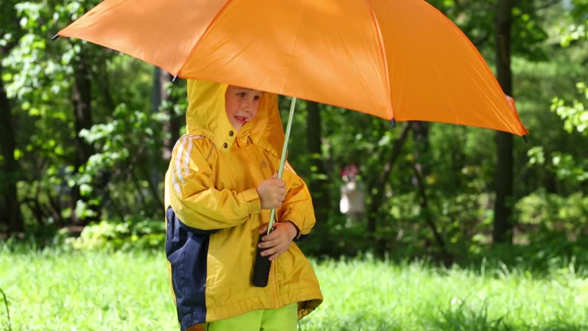 Smiling boy with orange umbrella stands on lawn in summer park - HD stock footage clip