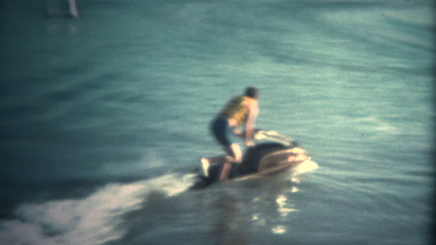 (Super 8 Vintage) Man Attempting to Ride JetSki Fail.  A retro super 8mm reel-to-reel home movie film professional clean and captured in full 4k (3840x2160 UHD) resolution plus footage restoration.