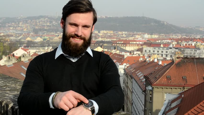 young handsome man with full-beard (hipster) point to watch (time) - city in background