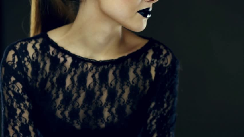 Part of woman's face with black lips turning her head on camera slowly and gives a blow kiss. Shallow depth of field