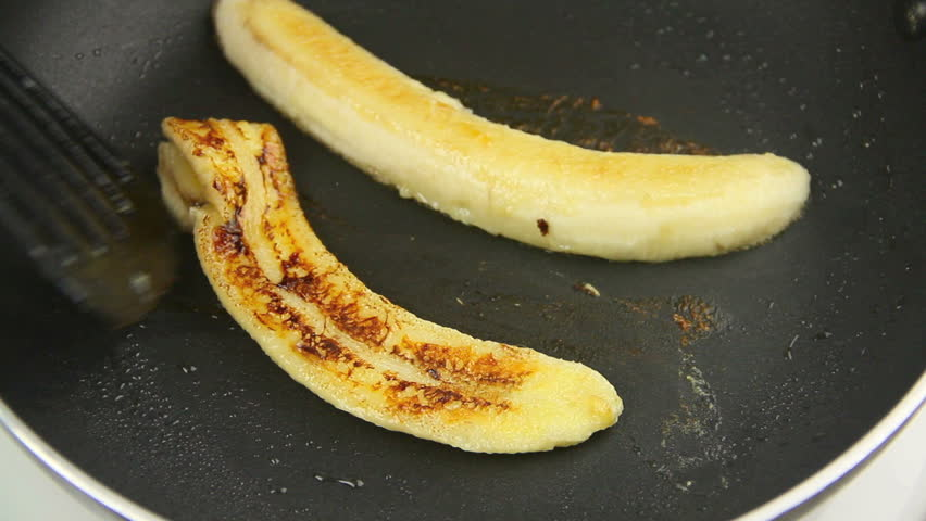 Slices of fresh banana being fried and turned over in a pan with a spatula.