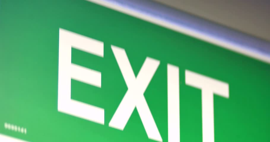 Footage of an exit sign-the shot moves from the top to the bottom
